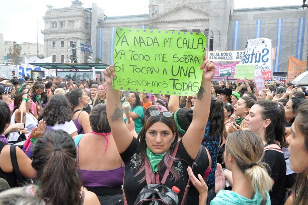 """Una chica posa frente al Congreso argentino con un cartel que reza: """"Ya nada me calla, todo me sobra, si tocan a una respondemos todas"""". (A. D)"""