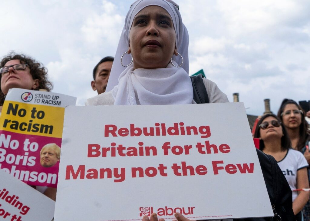Supporters hold placards as Britain's opposition Labour party leader Jeremy Corbyn addresses a rally calling for a General Election now, in Parliament Square, central London on July 25, 2019.